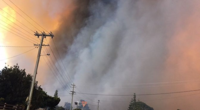 Flames come close to a home in Tathra.  Image:ABC News: Peta Doherty